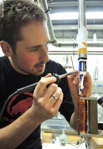 Der Doktorand David Zielke verlötet elektrische Zuleitungen an einem Messeinsatz für die Bestimmung des elektrischen Widerstands bei tiefen Temperaturen und hohen Drucken; Foto: AG Lang