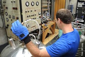 Lars Postulka, Doktorand im SFB/TR 49, transferiert flüssigen Stickstoff zur Vorbereitung eines Experimentes, das die spezifische Wärme bei sehr tiefen Temperaturen bestimmt; Foto: AG Lang