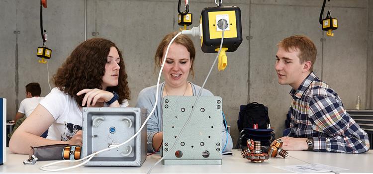 Doktorand Michael Wenzel betreut im Schülerlabor Elektromobilität zwei Schülerinnen bei Experimenten zu Elektromotoren; Foto: Lecher