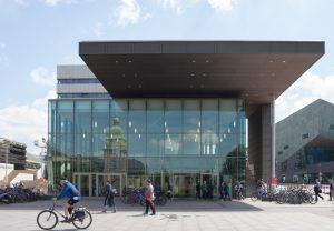 Das Eingangsgebäude karo 5 der TU Darmstadt am Karolinenplatz. In der Glasfassade spiegelt sich das Hessische Landesmuseum Darmstadt. Foto: Jan-Christoph Hartung