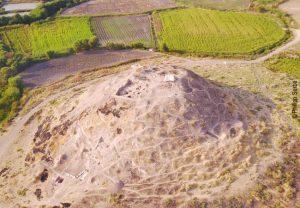 Luftaufnahme des Fundplatzes von Süden. Zu erkennen sind die Grabungsareale auf der Kuppe und am südwestlichen Hang sowie die kleine Sondage am südöstlichen Hang. Foto: Philipp Serba
