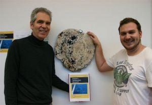 Prof. Eberhard Gischler und sein Doktorand Dominik Schmitt mit dem letzten Stück des 1970 von Jacques Cousteau geborgenen Stalaktiten aus dem Blue Hole. Foto: Daniel Parwareschnia