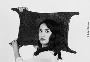 Francesca Meneghetti, Doktorandin der Archäologie, beim Tragen eines Ochsenhautbarrens; Foto: Julian Gerchow
