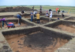 Trans-Ural. Bronzezeitliche Reihenhaussiedlung Konopljanka-2 mit einem verfüllten Brunnenschacht im Vordergrund. Grabung 2018